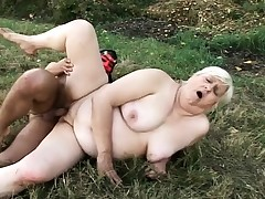 Sexually aroused mature blonde has a masked stud banging her cunt in the outdoors